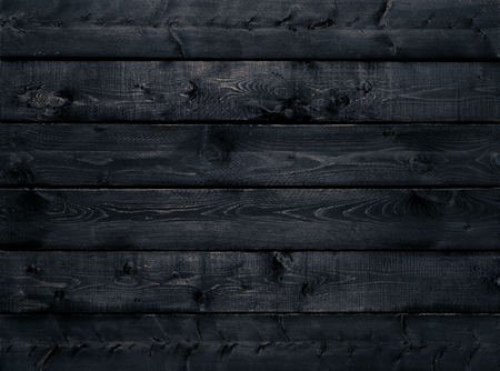 Dark black wood texture background viewed from above. The wooden planks are stacked horizontally and have a worn look. This surface would be great as design element for a wall, floor, table etc…