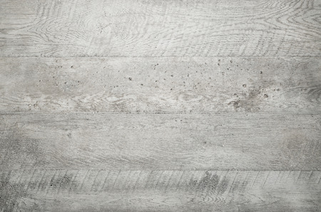 Grey wood texture background viewed from above. The wooden planks are stacked horizontally and have a worn look.