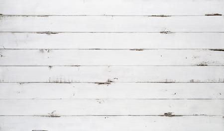 Bekymrad vit trästruktur bakgrund sedd ovanifrån. Träplankarna staplas horisontellt och har en sliten look.