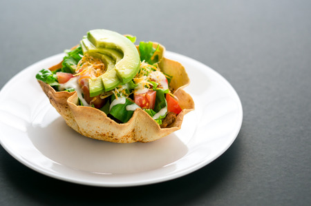 tex mex: A taco salad in tortilla bowl is a fun and colorful way to eat mexican food. Made with fresh ingredients such as avocado, tomatoes, green salad, cheese and delicious sour cream vinaigrette. Stock Photo