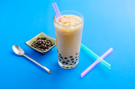 pearl tea: A glass of homemade milk tea bubbletea, with ice and tapioca balls (also called pearls). Bubble tea is a refreshing drink,  very popular in taiwan and increasingly elsewhere in the world.