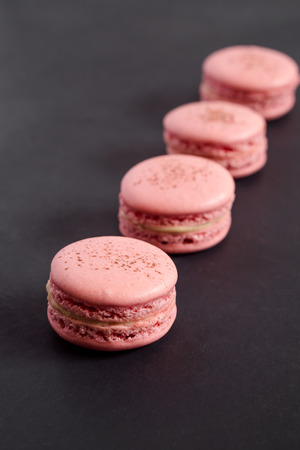Strawberry macarons on a dark background. Macarons are delicate french pastries consisting of two round meringue cookies and a sweet filling in the center. Light & crisp, these are the perfect luxurious dessert.