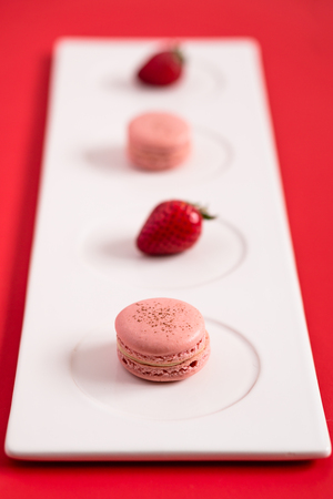 Strawberry macarons on a red background. These romantic french pastries are made of two meringue cookies and a sweet filling. Light & crisp, these are the perfect valentine day dessert.