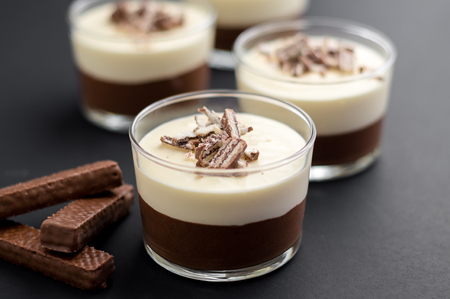 No-bake layered chocolate mousse and cheesecake with chocolate covered wafer cookie crumbs topping. In clear glass dessert bowls. On dark background. Great recipe, creamy, light and not too sweet!