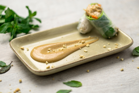 Delicious creamy peanut butter dipping sauce on a plate with crunchy peanut crumbs and Vietnamese spring rolls on the side. Peanut butter sauce is often used in Asian  Vietnamese cuisine.