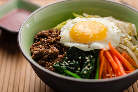 Bibimbap is a classic Korean meal. A bowl of rice is topped with seasoned vegetables, meat and a sunny side up fried egg on top. Spicy chili sauce can be added to finish off this savoury Asian dish.