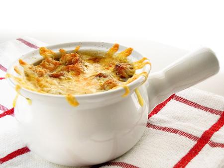 하얀 그릇에 양파 수프입니다. 주로 쇠고기 국물에 천천히 요리 된 양파로 이루어져 있으며 보통 빵이나 croutons의 떠 다니는 조각에 구워진 치즈가 제