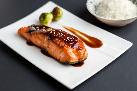 Japanese cuisine inspired dinner consisting of a grilled salmon fillet glazed in delicious teriyaki sauce (soy sauce base). Brussel sprouts and white rice as sides. Banco de Imagens