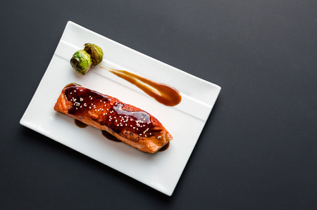 plating: Japanese cuisine inspired dinner consisting of a grilled salmon fillet glazed in delicious teriyaki sauce (soy sauce base). Brussel sprouts and white rice as sides. Stock Photo
