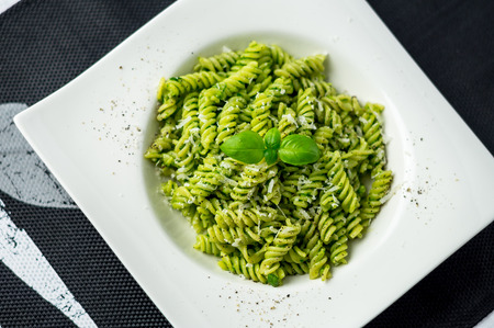 Rotini pesto pasta top view. Rotini pasta with basil pesto sauce, grated parmesan cheese and fresh pepper. This Italian dish makes a delicious meal by itself or can be used as a pasta salad side. 版權商用圖片