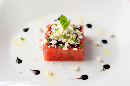 Watermelon salad on white. This watermelon cubes salad is made with greek feta cheese crumbs, olive slices, mint, olive oil and balsamic vinegar. So refreshing, the perfect food for the summer!