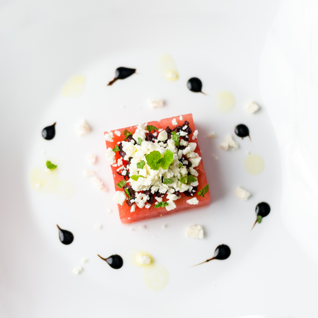 Watermelon feta top view.  This watermelon cubes salad is made with greek feta cheese crumbs, olive slices, mint, olive oil and balsamic vinegar. So refreshing, the perfect food for the summer!