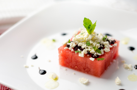 Fresh watermelon salad starter. This watermelon cubes salad is made with greek feta cheese crumbs, olive slices, mint, olive oil and balsamic vinegar. So refreshing, the perfect food for the summer!