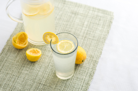 Freshly squeezed lemonade juice glass. Lemonade is traditionally a homemade drink made with squeezed lemon, water and sugar, a simple recipe for a quick refreshing summer drink packed with vitamin c.