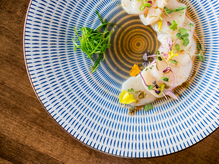 Scallops sashimi from above. Fresh raw scallops sashimi dish. Sashimi is a Japanese cuisine delicacy consisting of sliced raw meat (usually fish and seafood) often served in sushi restaurants.