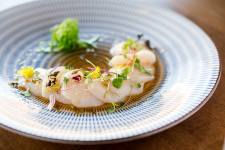 plating: Raw scallops sashimi seafood dish. Fresh raw scallops sashimi dish. Sashimi is a Japanese cuisine delicacy consisting of sliced raw meat (usually fish and seafood) often served in sushi restaurants. Stock Photo