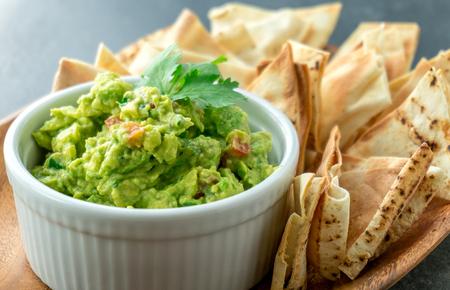 Mexická guacamole jídlo. Guacamole je dip na avokádo, tradičně mexické (aztécké) jídlo. Zdravé a snadno vyrobené doma s několika jednoduchými přísadami. Vynikající jako večírek nebo v baru .. Reklamní fotografie