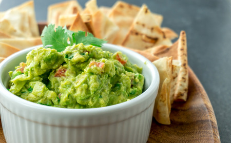 Guacamole close-up view. Guacamole is a avocado based dip, traditionally a mexican (Aztecs) dish. Healthy and easy to make at home with a few simple ingredients. Excellent as party food or at bars.. 版權商用圖片