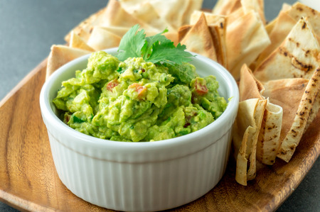 Fresh guacamole bowl. Guacamole is a avocado based dip, traditionally a mexican (Aztecs) dish. Healthy and easy to make at home with a few simple ingredients. Excellent as party food or at bars.. Stock Photo