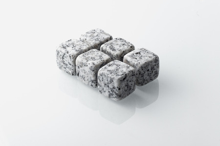 Set of six spirit chilling stones. Soapstone rocks are carved in cubes to be used as drink chiller (whisky, bourbon ...) Various type of raw minerals produces different colors, such as marbled grey. Stock Photo