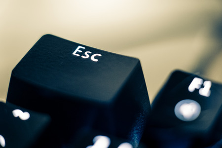 Macro photo of the escape key on a mechanical switch keyboard. The ESC letters are etched on plastic ABS keycaps to reveal the white led backlight. The other keys are out of focus in the background. Stock Photo