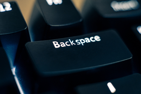 Macro photo of the backspace key on a mechanical switch keyboard. The letters are etched on black plastic ABS keycaps to reveal the white led backlight. Other keys are out of focus in the background.
