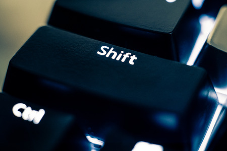 Macro photo of the shift key on a mechanical switch keyboard. The letters are etched on black plastic ABS keycaps to reveal the white led backlight. Other keys are out of focus in the background.