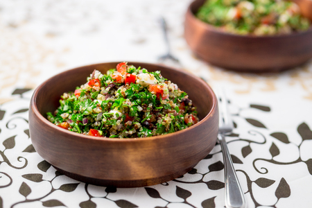 Healthy vegetarian salad bowl. This healthy dish mixes tabbouleh & greek style salads, using fresh parsley herb, olives, onions, feta and replacing the bulgur usually found in tabouleh with quinoa. Stock Photo