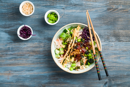 Hawaiian poke bowl flat lay view from above. Poke is a traditional Hawaiian dish influenced by japanese and asian cuisine. Ahi poke is made of raw tuna chunks tossed over rice & topped with vegetables