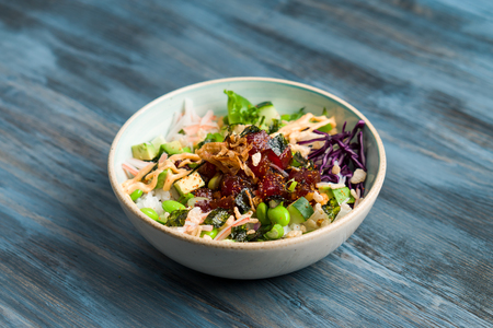 Hawaiian ahi tuna poke bowl centered view. Poke is a traditional Hawaiian dish influenced by japanese and asian cuisine. Ahi poke is made of raw tuna chunks tossed over rice & topped with vegetables.