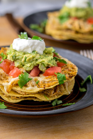 Stacked tostada dish closeup. Tostadas are a type mexican food, made with crispy fried corn tortillas covered with layers of various ingredients such as chicken, guacamole, cheese, sour cream & salsa.