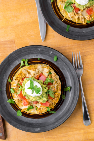 Tostada stack meal from above. Tostadas are a type mexican food, made with crispy fried corn tortillas covered with layers of various ingredients such as chicken, guacamole, cheese, sour cream & salsa