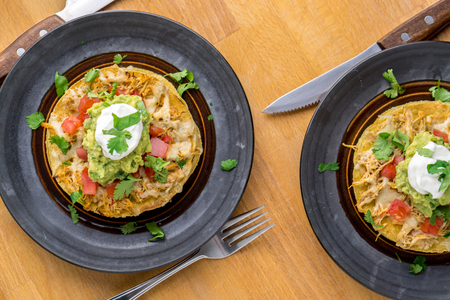 Tostadas, a Mexican food made with crispy fried corn tortillas covered with layers of various ingredients such as chicken, guacamole, cheese, sour cream Stock Photo