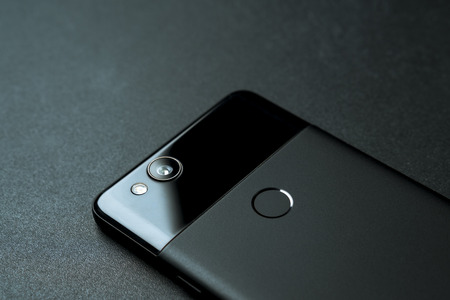 Montreal, Quebec, Canada - March 25, 2018: Backside view of a black Google Pixel 2. The smartphone is laying flat on a black mousepad background. The phone camera features a 12MB sensor and f1.8 lens