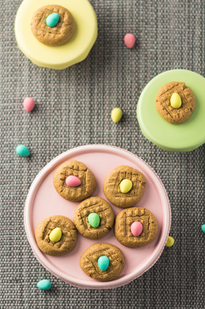 Easter cookies above flat top view. Homemade peanut butter cookies desserts with a Easter holiday twist! Chocolate easter eggs are added on top of each cookie. Served on colorful pastel cake stands.