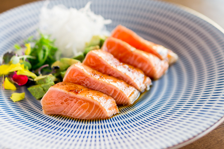 Salmon tataki dinner close-up. Slices of sashimi grade salmon seared lightly to keep the fish raw inside. This is a Japanese cuisine technique which is often used in gourmet fine dining restaurants.