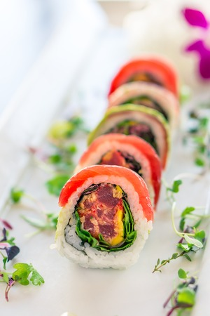 Fresh maguro maki sushi roll. A uramaki style sushi roll on a white plate. The raw sashimi tuna fish and rice are outside while nori is inside. This delicious meal is served in japanese restaurants.