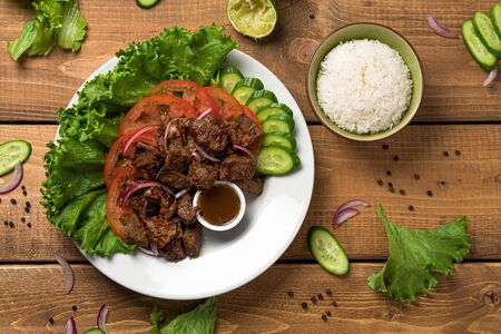 Bo Luc Lac dish on wooden background. Also named Lok Lak in cambodia or Shaking Beef in America. Tasty marinated sauteed beef cubes are served with fresh lettuce, tomatoes, cucumbers, onions and rice.