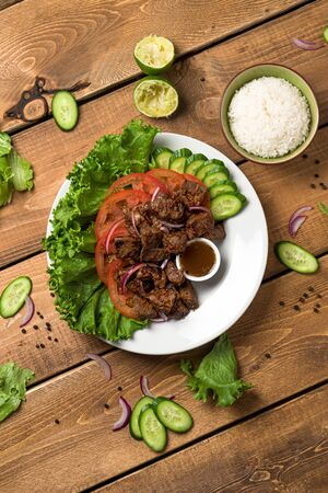 Bo Luc Lac in portrait orientation. Also named Lok Lak in cambodia or Shaking Beef in America. Tasty marinated sauteed beef cubes are served with fresh lettuce, tomatoes, cucumbers, onions and rice.