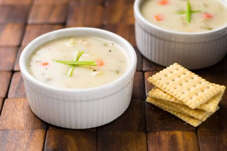 Clam chowder bowl with crackers. Traditionally from the United States, New England Clam Chowder is a delicious type of hearty and creamy soup. It commonly made with clams, potatoes, onions and celery.