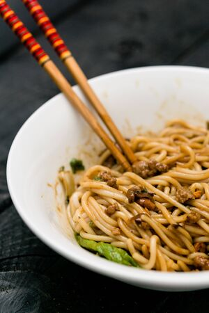 Dan Dan Noodle vertical view. Dan Dan Noodles is a spicy Szechuan cuisine dish commonly found in chinese street food. Ingredients include thick rice noodles, sichuan pepper, chili oil and ground pork. Imagens