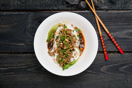 Dan Dan Noodles top view. Dan Dan Noodles is a spicy Szechuan cuisine dish commonly found in chinese street food. Ingredients include thick rice noodles, sichuan pepper, chili oil and ground pork. Stok Fotoğraf