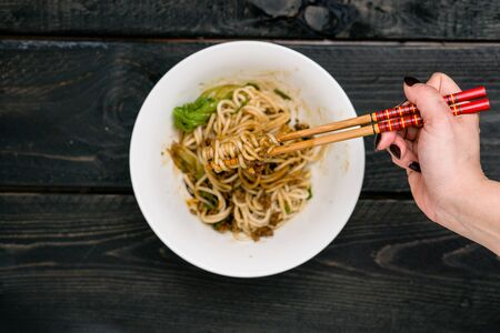Dandan Noodles on chopsticks. Dan Dan Noodles is a spicy Szechuan cuisine dish commonly found in chinese street food. Ingredients include thick rice noodles, sichuan pepper, chili oil and ground pork.