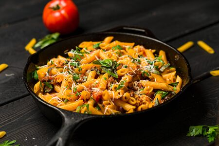 Pasta on dark background. This quick & delicious pasta meal is made with penne pasta, fresh tomato sauce and sausage. This italian inspired comfort food is cooked and served in a cast iron skillet.