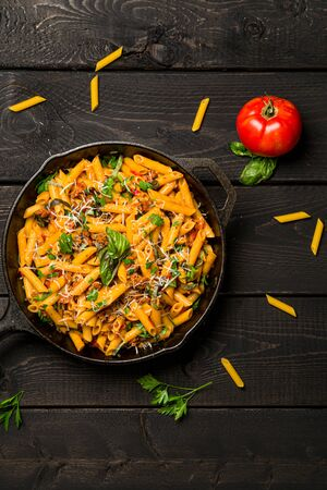 Pasta skillet dish top view. This quick & delicious pasta meal is made with penne pasta, fresh tomato sauce and sausage. This italian inspired comfort food is cooked and served in a cast iron skillet. Imagens