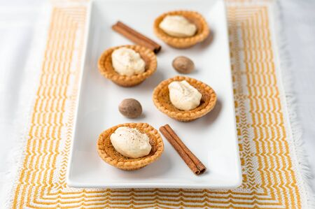 Mini butter tart with cream. Mini sugar pies (or butter tarts) with a crisp pastry crust, a sweet filling and pumpkin spice whipped cream on top. A tasty dessert for fall holidays like halloween! Stok Fotoğraf