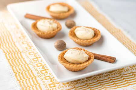 Homemade butter tart dessert. Mini sugar pies (or butter tarts) with a crisp pastry crust, a sweet filling and pumpkin spice whipped cream on top. A tasty dessert for fall holidays like halloween!