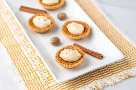 Sugar tartlet pastry dessert. Mini sugar pies (or butter tarts) with a crisp pastry crust, a sweet filling and pumpkin spice whipped cream on top. A tasty dessert for fall holidays like halloween! Stok Fotoğraf