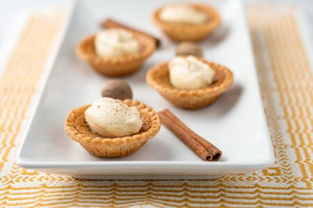 Sweet butter tart close-up. Mini sugar pies (or butter tarts) with a crisp pastry crust, a sweet filling and pumpkin spice whipped cream on top. A tasty dessert for fall holidays like halloween!