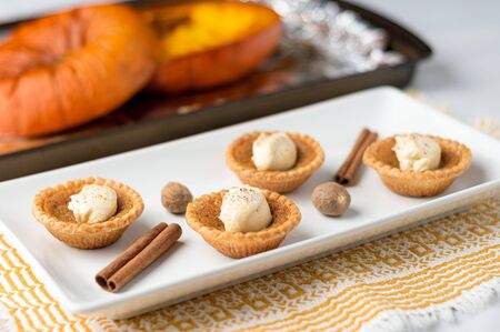 Pumpkin spice butter tart. Mini sugar pies (or butter tarts) with a crisp pastry crust, a sweet filling and pumpkin spice whipped cream on top. A tasty dessert for fall holidays like halloween! Stok Fotoğraf